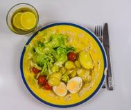 Vista superior de una ensalada con las patatas, los tomates de cereza y los huevos, ji Foto de archivo