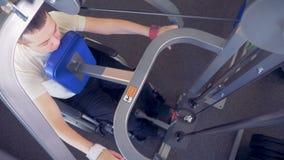 Vista superior de una máquina de la elevación-carga que es utilizada por un hombre perjudicado durante la fisioterapia metrajes