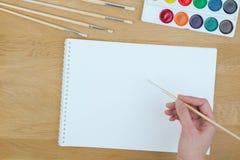 Vista superior de una mano con el cepillo de pintura, las pinturas de la acuarela y la hoja de papel en blanco Fotografía de archivo libre de regalías