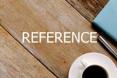 Vista superior de una taza de café, de cuaderno y de pluma en el fondo de madera escrito con REFERENCIA fotografía de archivo libre de regalías