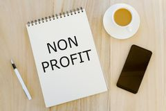 Vista superior de una taza de café, de teléfono móvil, de pluma y de cuaderno escritos con no concepto del beneficio, del negocio fotos de archivo libres de regalías