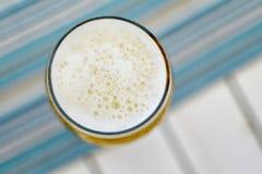 Vista superior de una taza espumosa de cerveza fría en un día de verano caliente en un re Foto de archivo