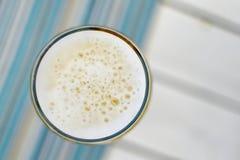 Vista superior de una taza espumosa de cerveza fría en un día de verano caliente en un re Fotos de archivo