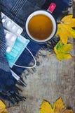 Vista superior de una taza de té, bufanda azul, termómetro, drogas y máscara y hojas faciales médicas en fondo de madera imagen de archivo