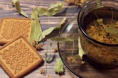 Vista superior de una taza de té de las flores del tilo Después en la tabla está una galleta y las flores secadas del tilo imagenes de archivo