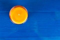 Vista superior de una vela anaranjada en fondo de madera azul Fotos de archivo