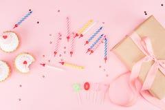Vista superior de velas coloridas, de queques saborosos do aniversário e de caixa de presente no rosa Foto de Stock Royalty Free