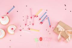 Vista superior de velas coloridas, de queques saborosos do aniversário e de caixa de presente no rosa Imagem de Stock