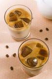 Vista superior de vidrios con leche y cubos de hielo grandes del café Fotos de archivo