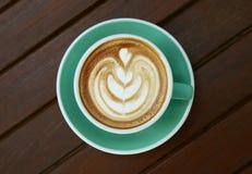 Vista superior del arte caliente del latte del capuchino del café en taza del color del jade en fondo de madera de la tabla fotografía de archivo