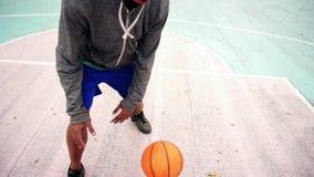 Vista superior del baloncesto practicante del hombre afroamericano irreconocible afuera Tiro a cámara lenta almacen de video
