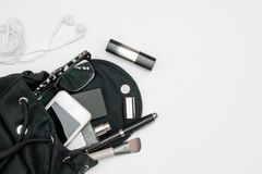 Vista superior del bolso del negro de la mujer abierto hacia fuera con smartphone, perfume, plumas, los cosméticos, el auricular  fotos de archivo