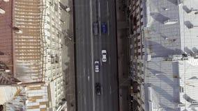 Vista superior del camino ancho con muchos coches que montan de diversos colores entre edificios almacen de metraje de vídeo