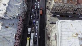 Vista superior del camino ocupado por completo de los coches que montan de diversos colores entre edificios almacen de video