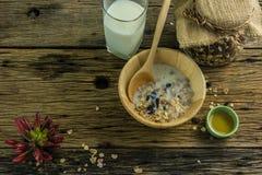 Vista superior del cereal y de la leche, abeja de la miel en la tabla de madera vieja Foto de archivo