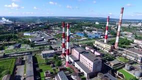 Vista superior del complejo industrial en ciudad con muchas chimeneas rojas y blancas de la planta el día soleado cantidad Indust metrajes
