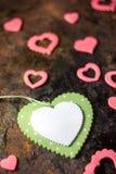 Vista superior del corazón verde con los corazones rosados sobre fondo negro Foto de archivo