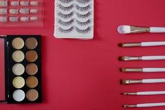 Vista superior del cosmético de los women's en fondo rojo foto de archivo