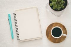 vista superior del cuaderno abierto con las páginas en blanco al lado de la taza de café en el fondo blanco aliste para añadir el Imagen de archivo