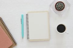 vista superior del cuaderno abierto con las páginas en blanco al lado de la taza de café en la tabla de madera aliste para añadir Fotografía de archivo