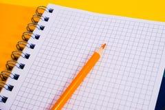 Vista superior del cuaderno en blanco espiral abierto con el l?piz en fondo amarillo del escritorio imágenes de archivo libres de regalías