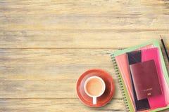 Vista superior del cuaderno, del pasaporte, del lápiz y de la taza de café en oficina Fotografía de archivo