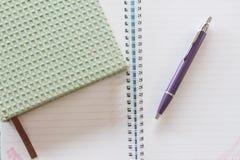 Vista superior del cuaderno verde, de la pluma y del cuaderno espiral Foto de archivo