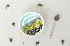 Vista superior del cuenco azul del smoothie del spirulina con los arándanos, el kiwi, las semillas de Chia y el granola en la tab foto de archivo