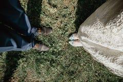Vista superior del ` de moda s del novio y de las piernas del ` s de la novia en calzado elegante en hierba Casarse concepto de l Imagen de archivo
