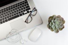 Vista superior del escritorio de oficina blanco de moda con el teclado, los auriculares blancos y los materiales de oficina fotos de archivo libres de regalías