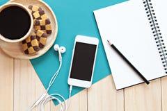 Vista superior del escritorio de trabajo con el cuaderno en blanco con el lápiz, el teléfono móvil, las galletas y la taza de caf Foto de archivo libre de regalías
