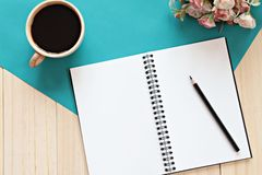 Vista superior del escritorio de trabajo con el cuaderno en blanco con el lápiz, la taza de café y las flores en fondo de madera Fotos de archivo libres de regalías