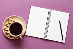 Vista superior del escritorio de trabajo con el cuaderno en blanco con el lápiz, las galletas y la taza de café en fondo del colo Fotografía de archivo libre de regalías
