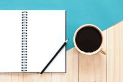 Vista superior del escritorio de trabajo con el cuaderno en blanco con la taza del lápiz y de café en fondo de madera Fotografía de archivo