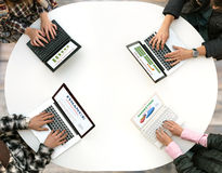 Vista superior del escritorio redondeado con cuatro ordenadores portátiles y manos de la gente que mecanografían en el teclado Fotos de archivo libres de regalías