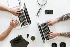 Vista superior del espacio de trabajo con dos ordenadores portátiles y el varón foto de archivo