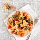 Vista superior del farfalle coloreado italiano de las pastas con albahaca y tomates fotos de archivo libres de regalías