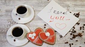 Vista superior del le necesito nota del mensaje y dos tazas de café con la galleta en forma de corazón del jengibre en una tabla  metrajes