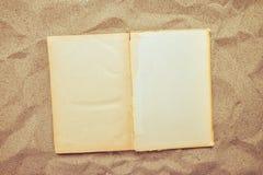 Vista superior del libro abierto del vintage en la playa arenosa fotografía de archivo