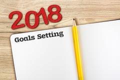 Vista superior del número rojo y de las metas del Año Nuevo 2018 que fijan con blan Foto de archivo