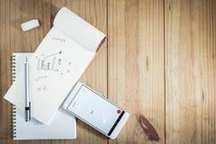 Vista superior del objeto de trabajo: lápiz gris en calendario abierto del cuaderno y del smartphone blanco en la tabla de madera Imagenes de archivo
