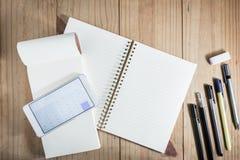 Vista superior del objeto de trabajo: lápiz gris y calculadora abierta app del smartphone blanco en el cuaderno blanco en fondo d Fotos de archivo libres de regalías