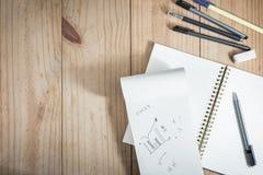 Vista superior del objeto de trabajo: lápiz gris y mucho pluma negra cerca del cuaderno blanco en la tabla de madera Fotografía de archivo
