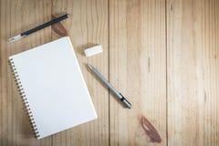 Vista superior del objeto de trabajo: lápiz gris y pluma negra cerca del cuaderno blanco en la tabla de madera Imagen de archivo