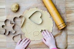 Vista superior del pan de jengibre del corte por las manos de los niños Imagenes de archivo