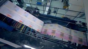 Vista superior del papel impreso fresco que se mueve a través de la máquina industrial almacen de video