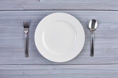 Vista superior del plato blanco con la bifurcación y la cuchara Imagen de archivo
