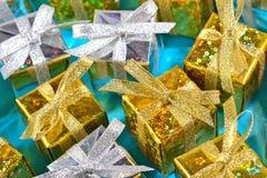 Vista superior del primer de oro y de plata de los regalos en un azul foto de archivo
