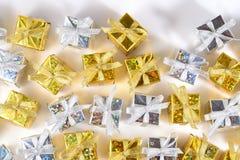 Vista superior del primer de oro y de plata de los regalos en un blanco imagen de archivo