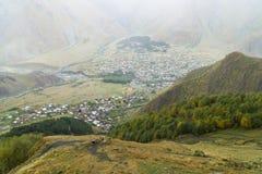 Vista superior del pueblo Stepantsminda de la iglesia de la trinidad de Gergeti, Georgia Fotografía de archivo libre de regalías